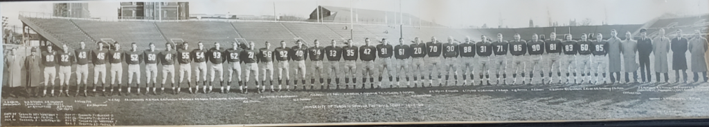 In this 1959 photo, 26 men in football uniform stand in a line across a football field.