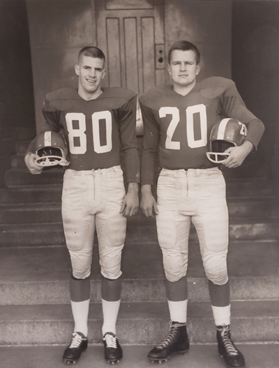 In a 1961 photo, Ron Crawford and Doug Boyd stand wearing football uniforms and holding their helmets under their arms.