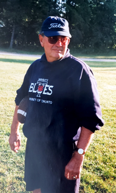 Ron Crawford stands on a grassy field wearing a Varsity Blues sweatshirt and holding a football.