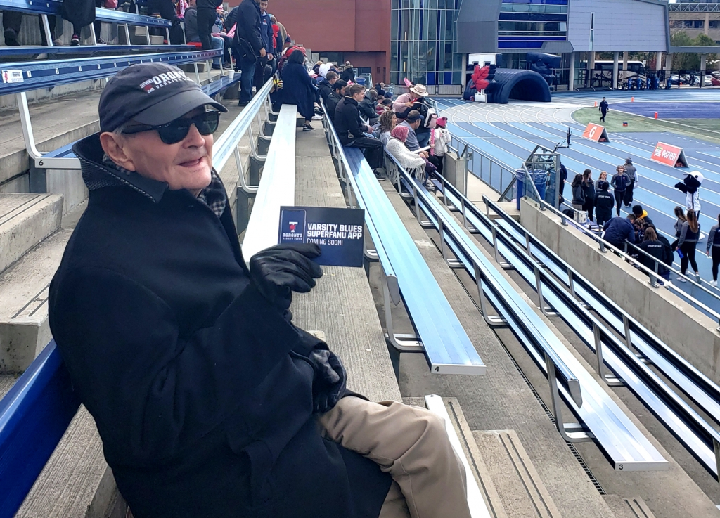 Ron Crawford sits in the stands at Varsity stadium and holds up his Varsity Blues Superfan pass.